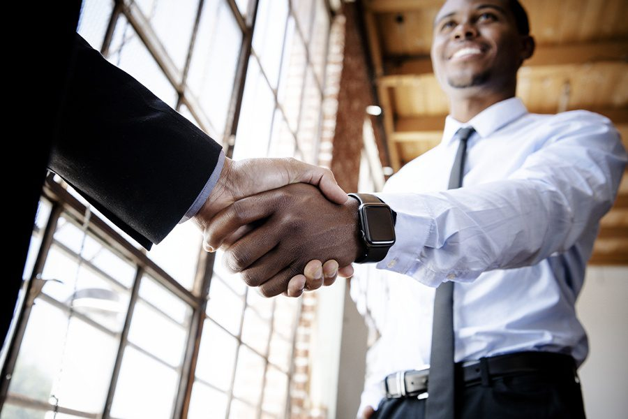 About Our Agency - Businessmen Shaking Hands at Emerge Insurance Agency After a Successful Business Meeting