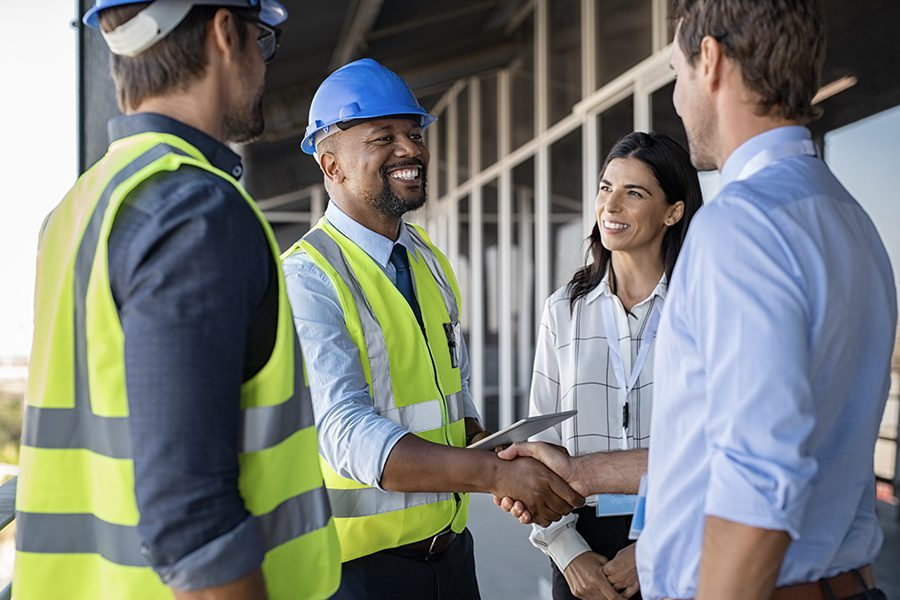 Specialized Business Insurance - Engineers and Architects in Conversation and Shaking Hands at Building Site