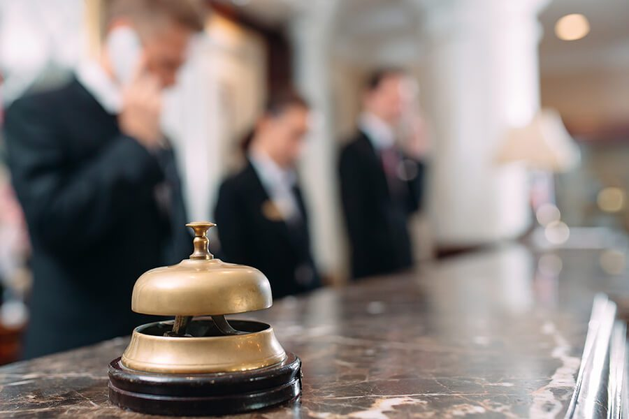 Hospitality Insurance - Front Desk Associate on the Phone with a Bell on the Desk of a Luxury Hotel