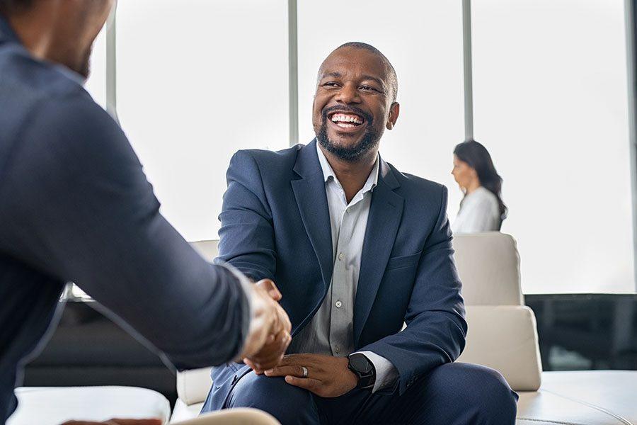Contact - Smiling Businessman Shakings Hands with His Colleague in the Office
