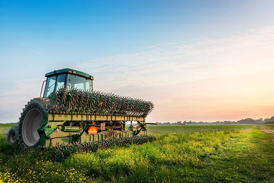 Farm Insurance - View of Modern Tractor Parked in Field of Crops