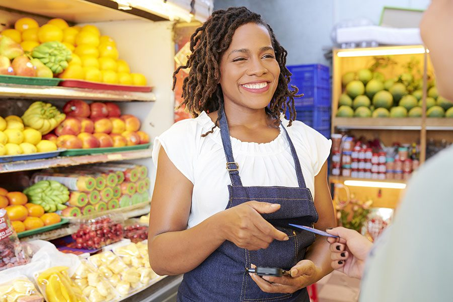 Retail Business Insurance - Smiling Grocery Store Worker Taking Credit Card from Customer