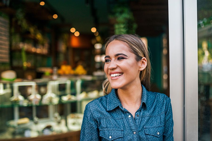 Business Insurance - Portrait of Smiling Small Business Owner Standing in Her Shop