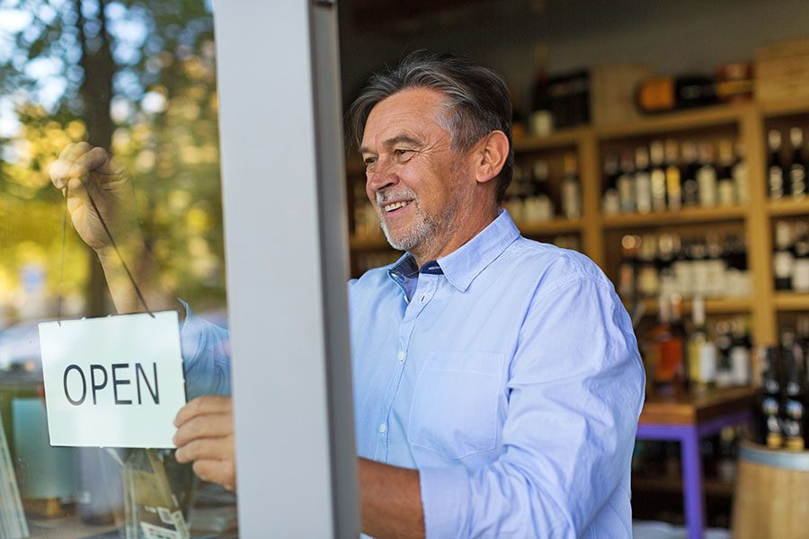Business Insurance - Mature Wine Shop Owner Hanging Up Open Sign On Front Door