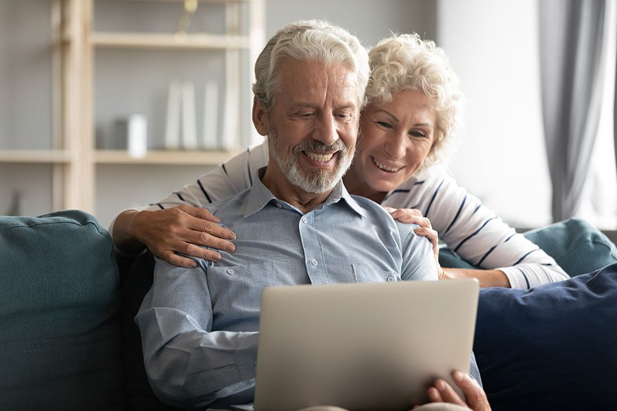 Client Center - Smiling Elderly Couple Sitting At Home Using Their Laptop