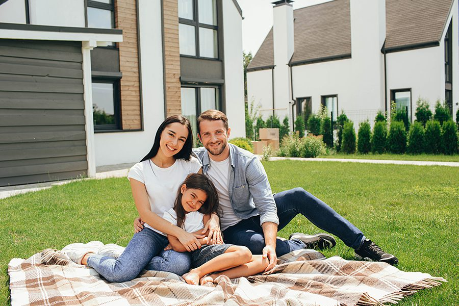 Blog - Family sitting on Lawn in the Backyard with a Modern House in the Background