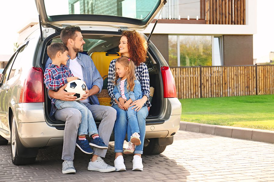 Personal Insurance - Young Family with Children Sitting in Their Car Trunk Near Their Family Home on a Summer Day