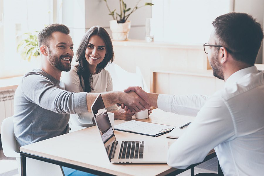 Client Center - Smiling Couple Shaking Hands With Their Insurance Agent In Office