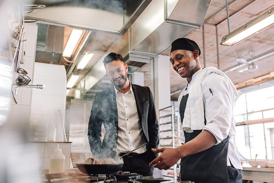 Specialized Business Insurance - Smiling Young Chef Cooking For Restaurant Owner