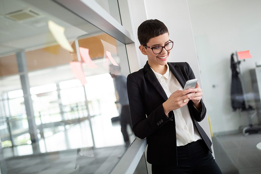 Client Center - Portrait of a Business Woman on a Her Phone Accessing Important Account Information in s Modern Office