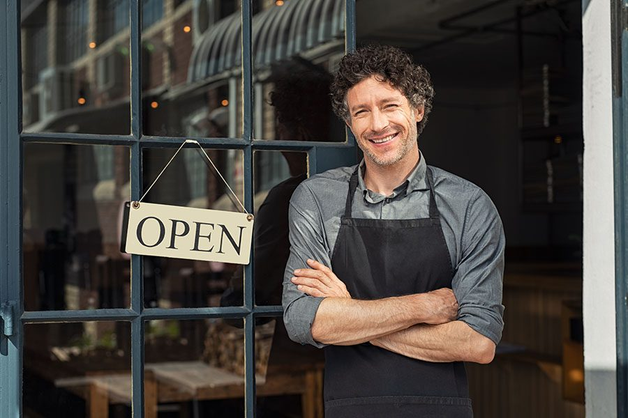 Business Insurance - Portrait of Smiling Business Owner Standing in Front of His Restaurant