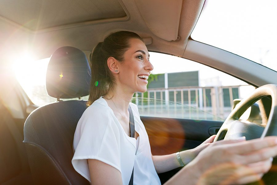 Insurance Quote - Portrait of Smiling Young Woman Driving in Her Car