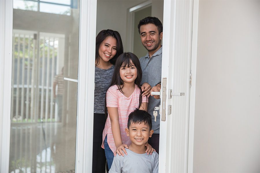 Personal Insurance - Smiling Family Standing in Front of Open Door in Their Home
