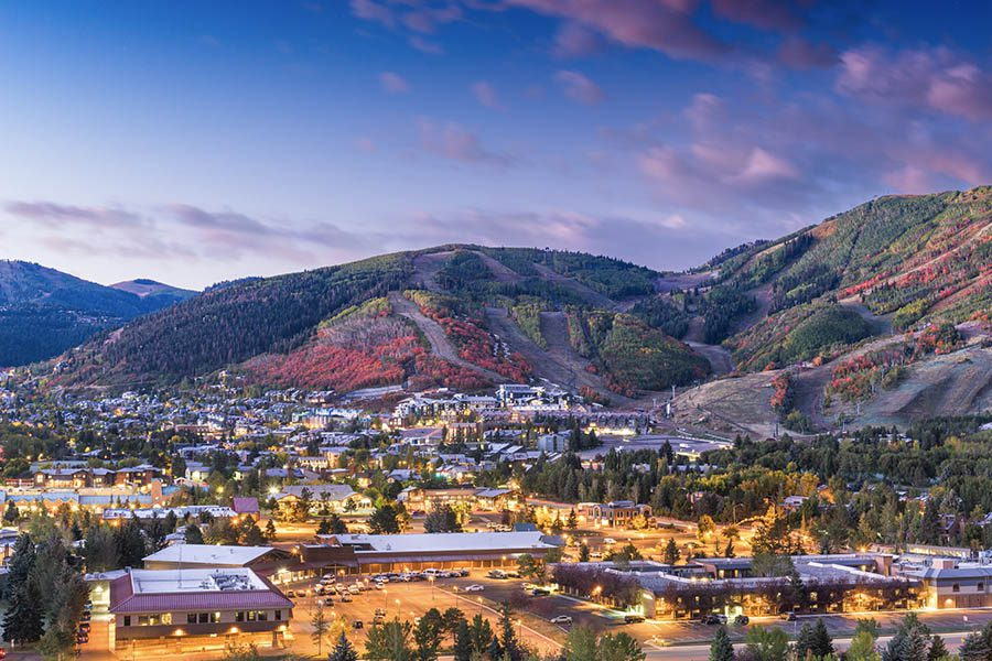 SentryWest Insurance - Park City UT Insurance - Beautiful Birds Eye View Of Park City Utah At Dawn With Purple Skys and Glowing Lights