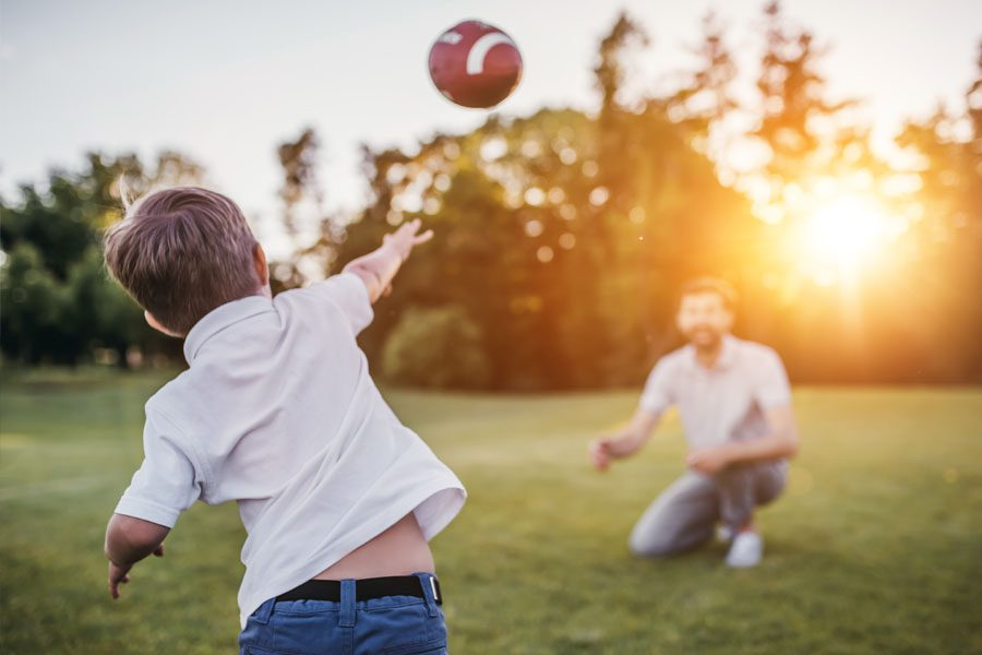 About Our Agency - Father and Son Throwing the Football in the Backyard