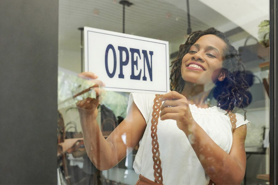 Business Insurance - Woman Opening Up Her Small Business for the Start of Business