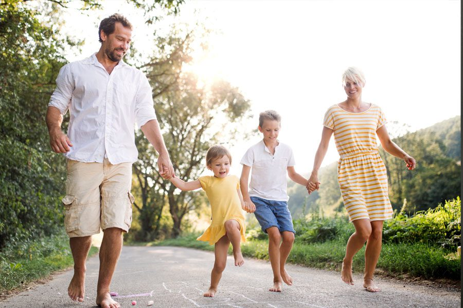 Personal Insurance - Family Walking Down an Outdoor Bike Path Playing Hopscotch