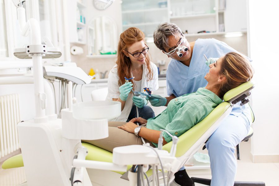 Group Dental Insurance - Dentist and Dental Assistant Performing a Cleaning