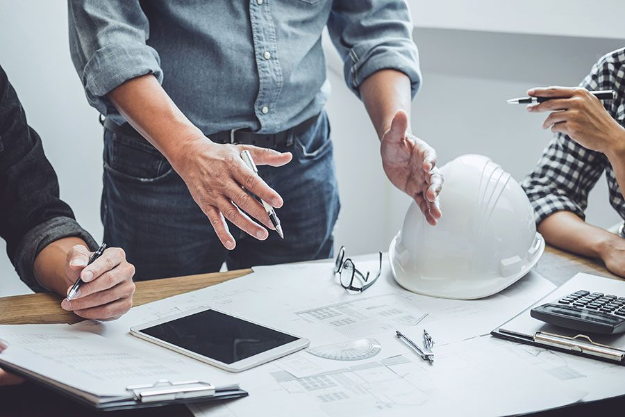 Specialized Business Insurance - Men Contractors Working at Desk with Papers and iPad