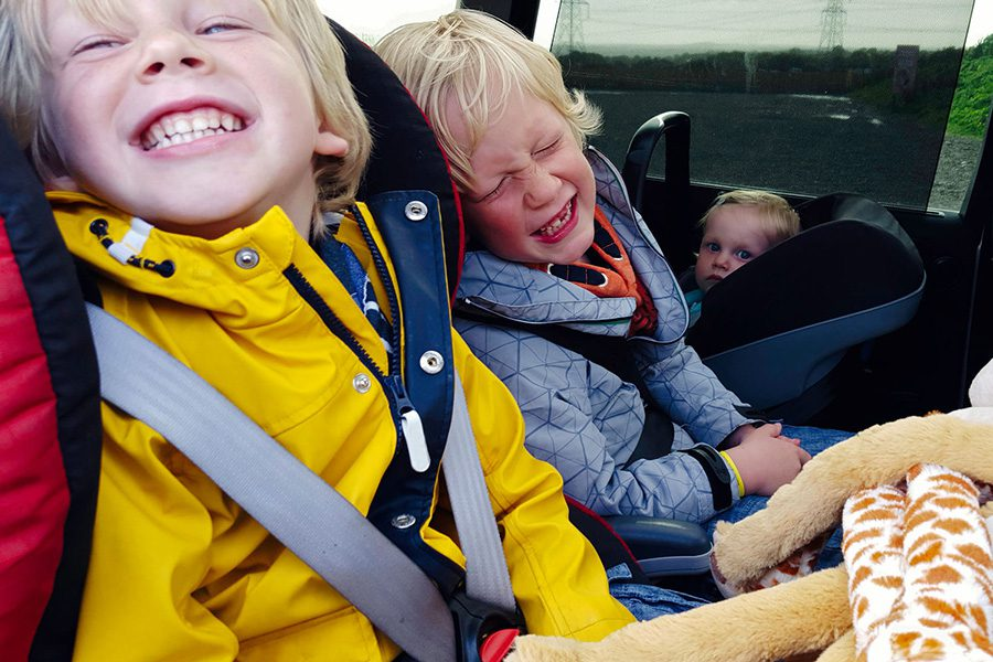 Auto Insurance - Kids Smiling and Laughing while Sitting in Car