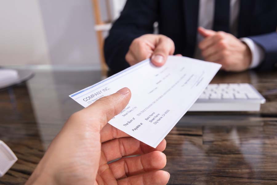 Payroll Solutions - Man Handing Co Worker a Check for Work for the Week