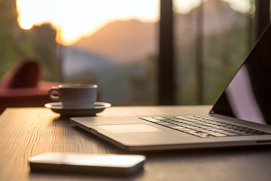 Local Resources - Phone Laptop and Coffee Cup On A Desk With The Sunrise In The Background Over The Mountains