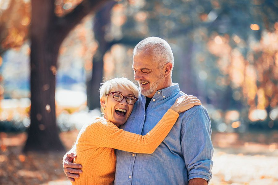 Contact - Elderly Couple Embracing While Going On Walk In The Forest