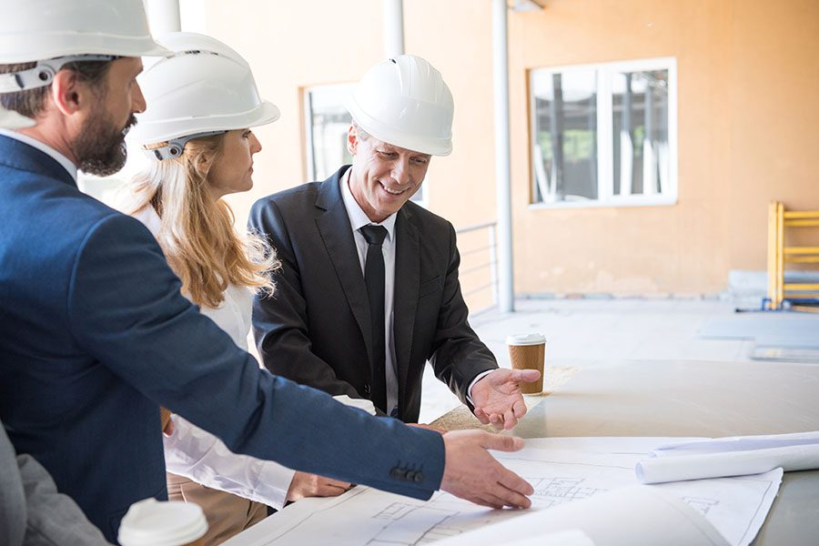 Specialized Business Insurance - Contractors In Suits Discussing Building Plans On Jobsite