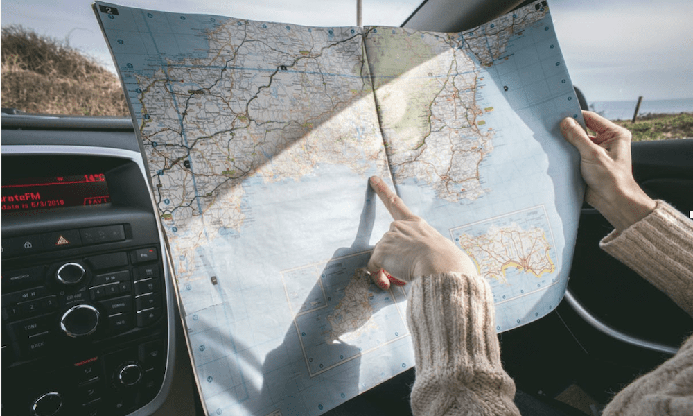 Automobile Insurance - a person on a road trip, reading a map