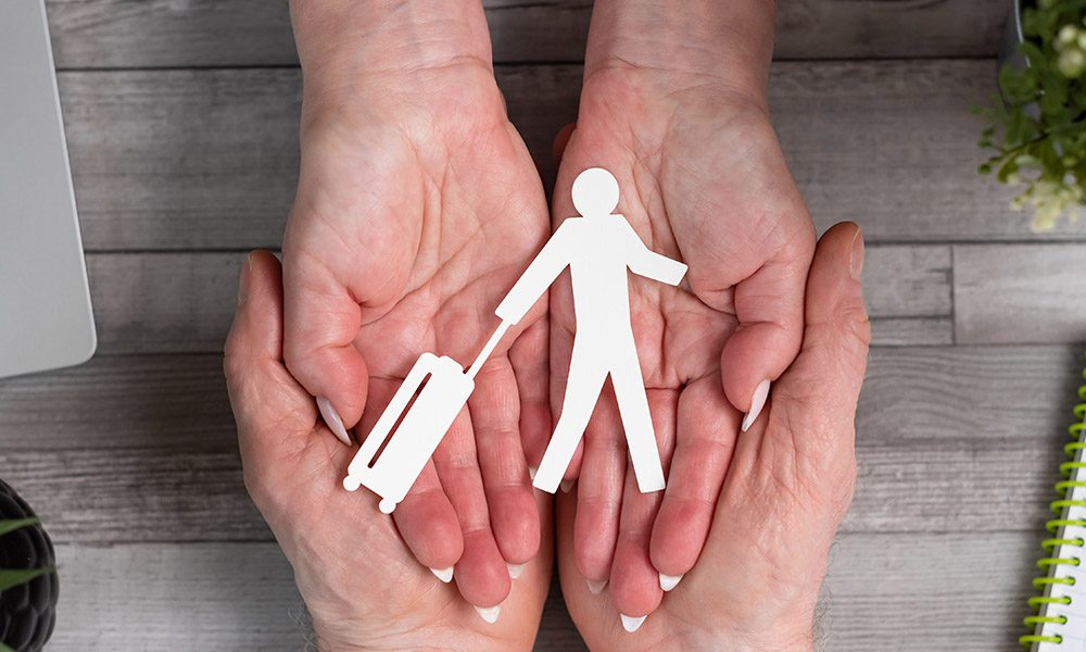 Blog - Paper Person Walking with Suit Case Held Within Man and Woman Hands