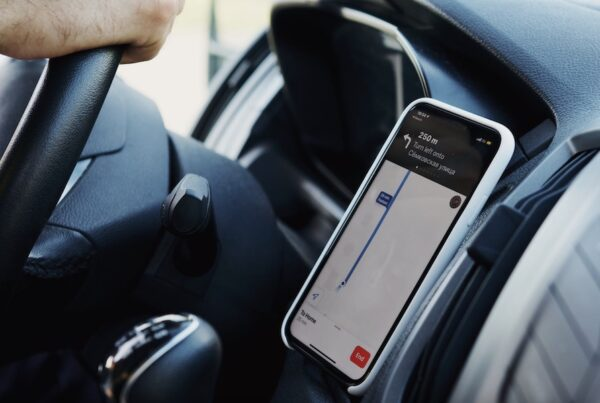 Image of a person driving a car with a smartphone app open on their phone on the dashboard while driving.