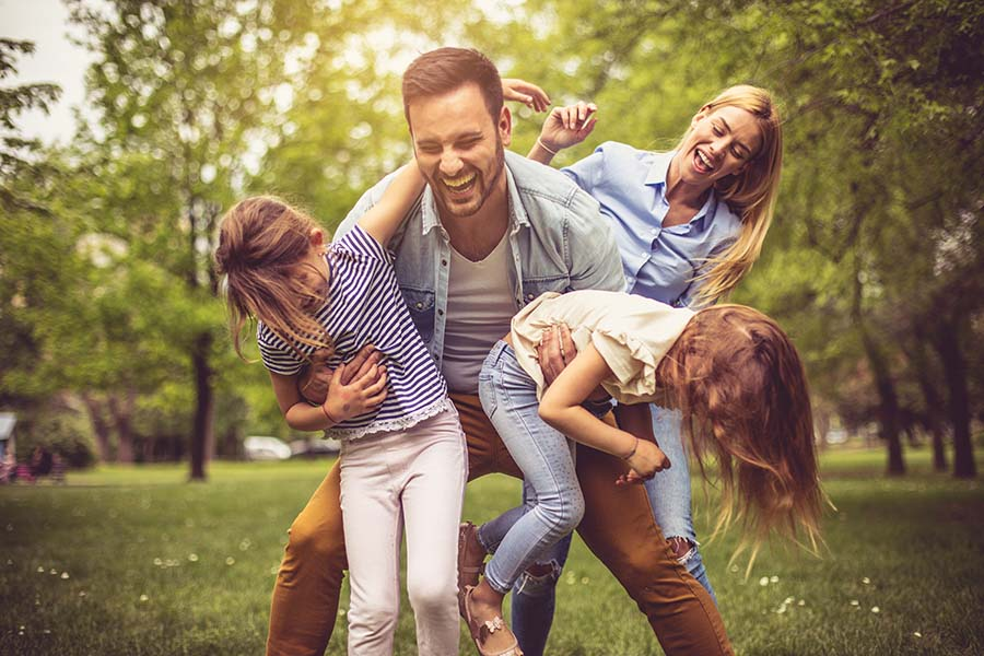 Personal Insurance - Family Having Fun Playing Outside In The Backyard On Warm Day