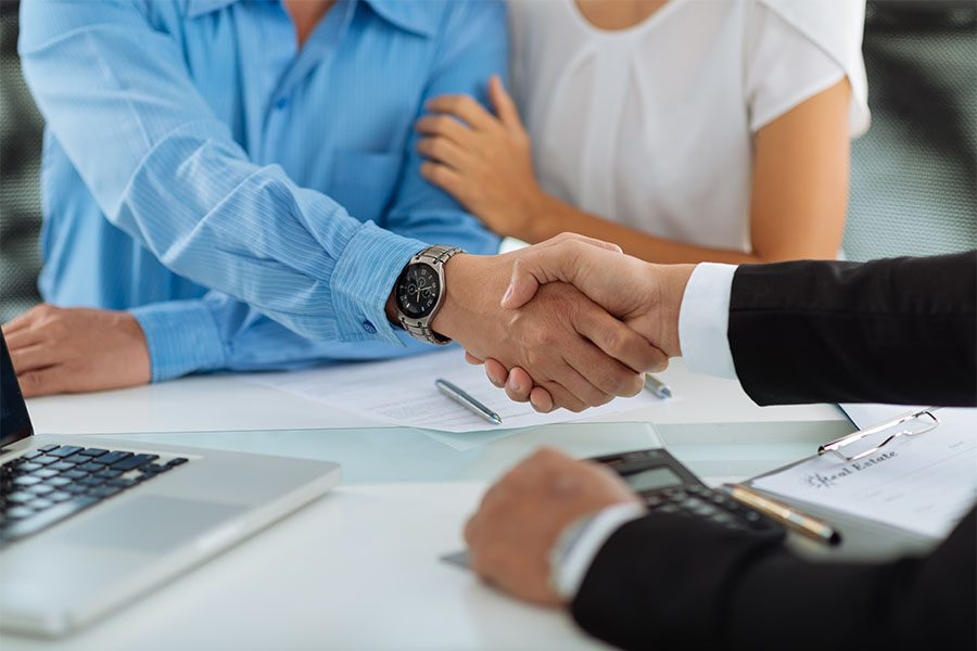 About Our Agency - Insurance Agent Shaking Hands with Couple in the Office