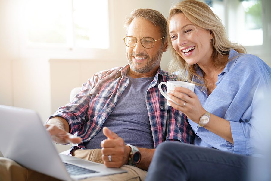 Client Center - Smiling Mature Couple Sitting at Home Using Their Laptop