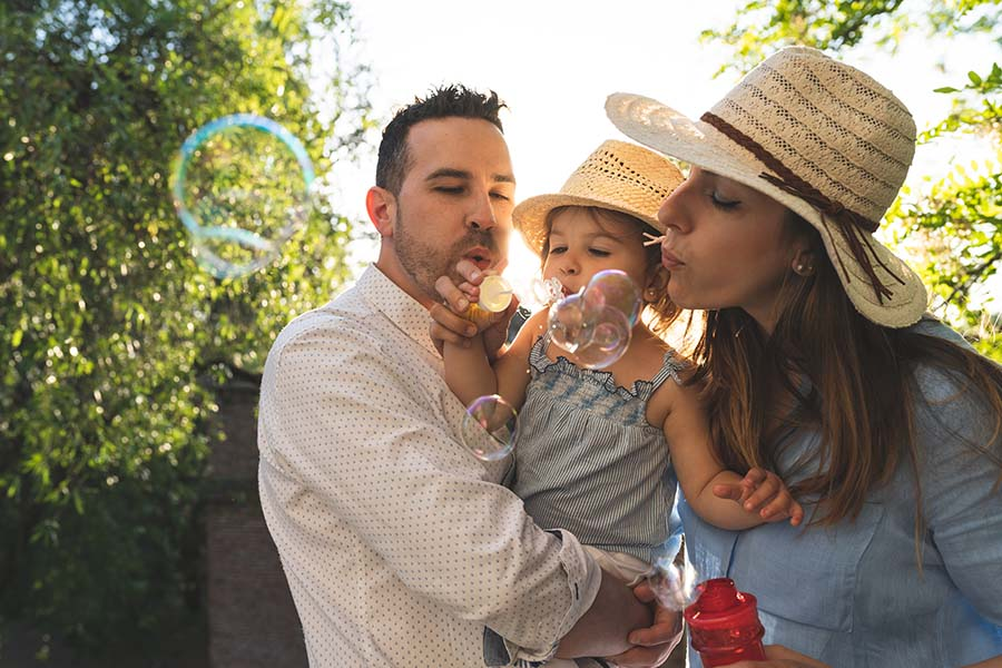 Personal Insurance - Parents Blowing Bubbles with Their Young Daughter Outside on Warm Summer Day