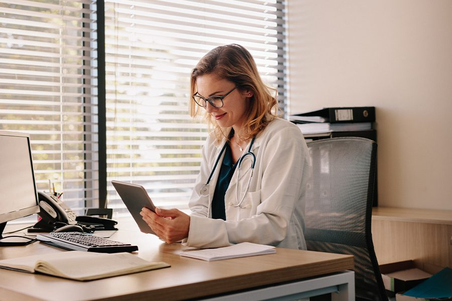Employee Benefits - Female Doctor Working at Her Desk and Charting on Her Digital Tablet