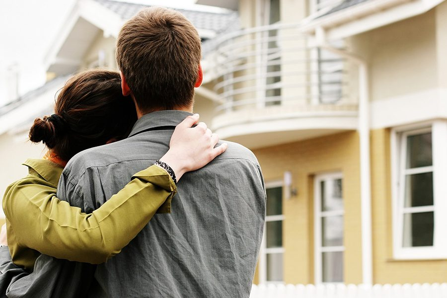 Personal Insurance - Couple in Front of a Newly Purchased Beachfront Home Blurred in the Background