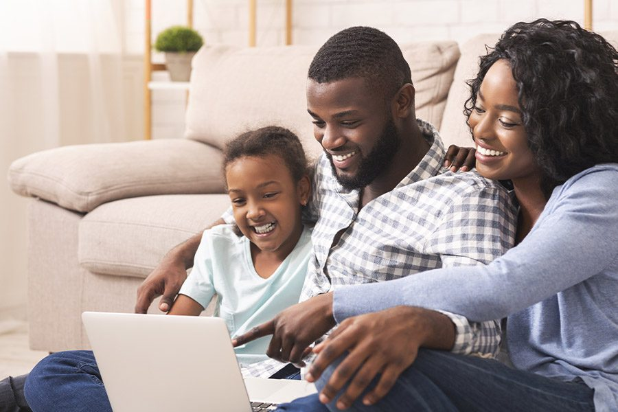 Blog - Joyful Family Using a Laptop at Home Together While Sitting on the Floor in Front of Their Couch