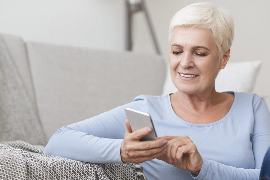 Client Center - Image of Senior Woman Using Her Phone to Easily Access Important Insurance Account Information