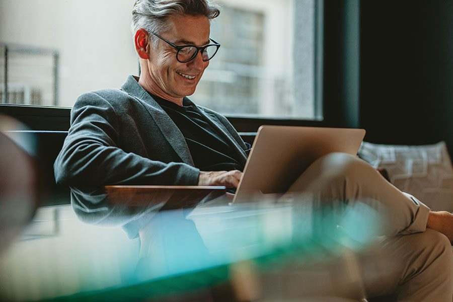 Blog - Smiling Mature Man Sitting On Couch In Office Reading On His Laptop