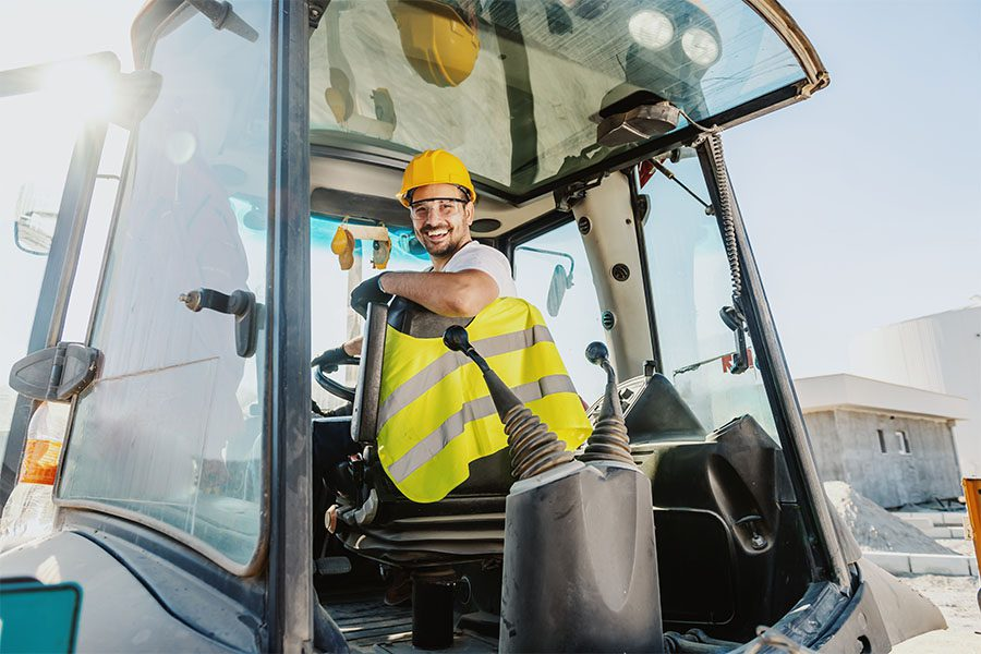 Business Insurance - Happy Construction Worker Sitting In An Excavator Truck