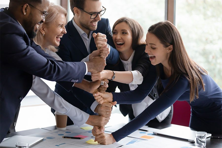 Contact - Group Of Excited Employees Stackign Their Hands Together On The Table In Office