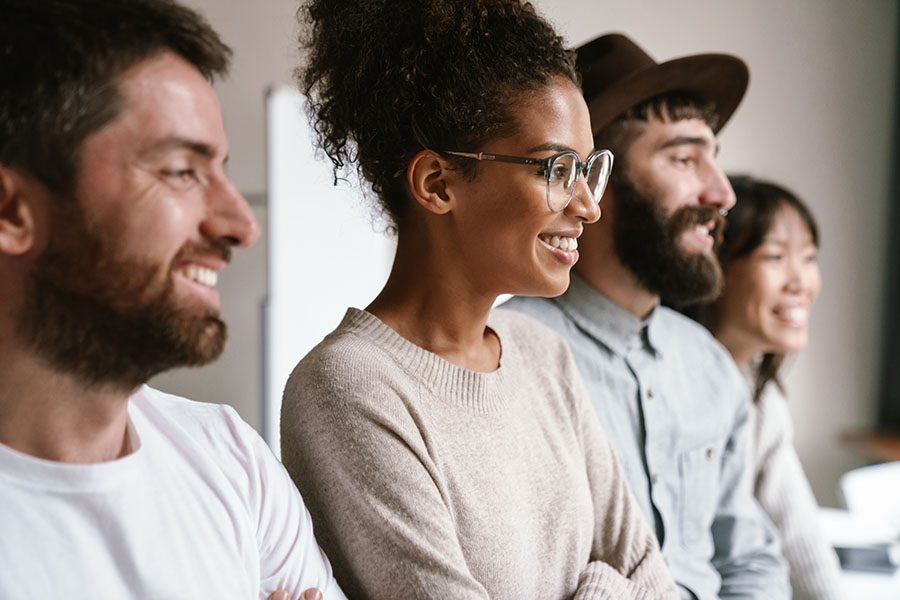 Employee Benefits - Group Of Smiling Employees Standing In The Office