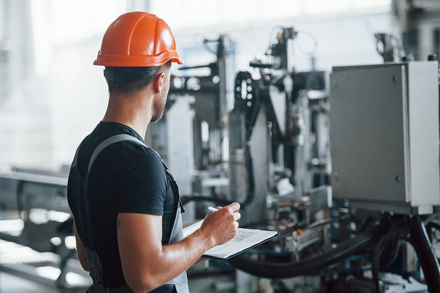 Specialized Business Insurance - Factory Worker Inspecting Manufacturing Machinery