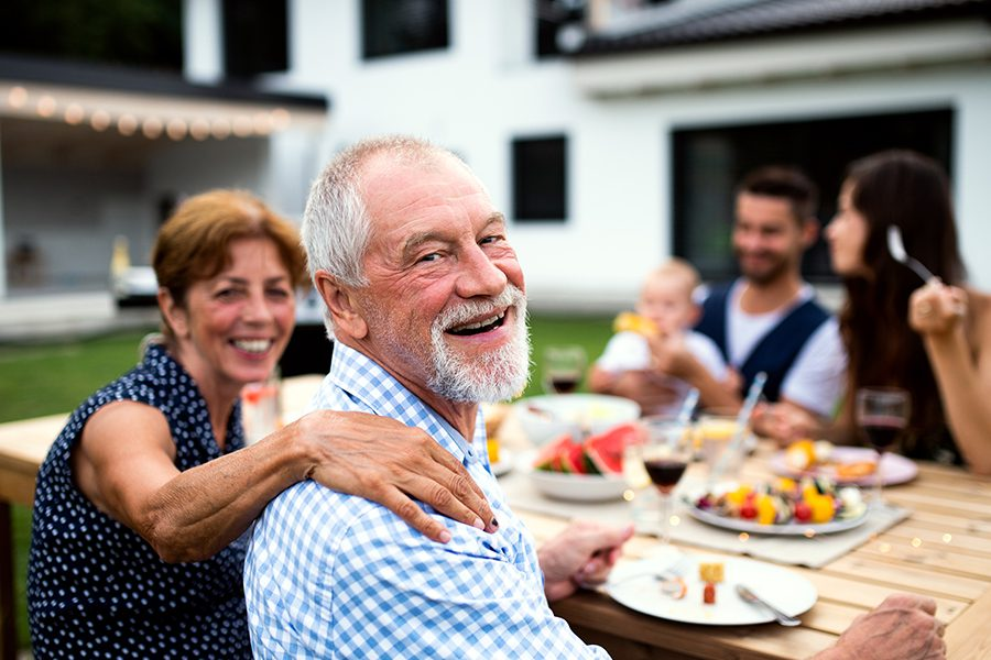 Blog - Portrait of a Family Sitting at the Table Outside of Their Family Home Having a Summer Barbecue