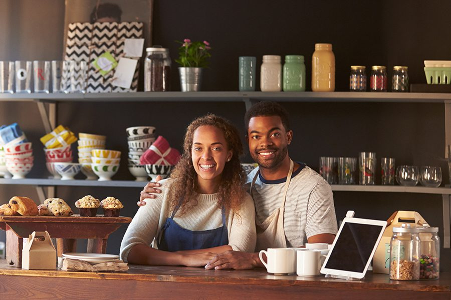Business Insurance - Happy Smiling Couple Working at The Counter of Their Local Coffee Shop Business