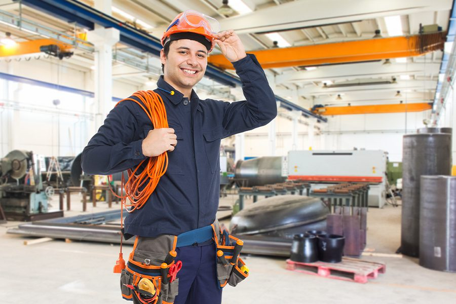 Contractor Insurance - Man Smiling in a Factory Warehouse While Holding Wiring Equipment and Wearing a Hardhat. Toolbelt and Other Protective Gear