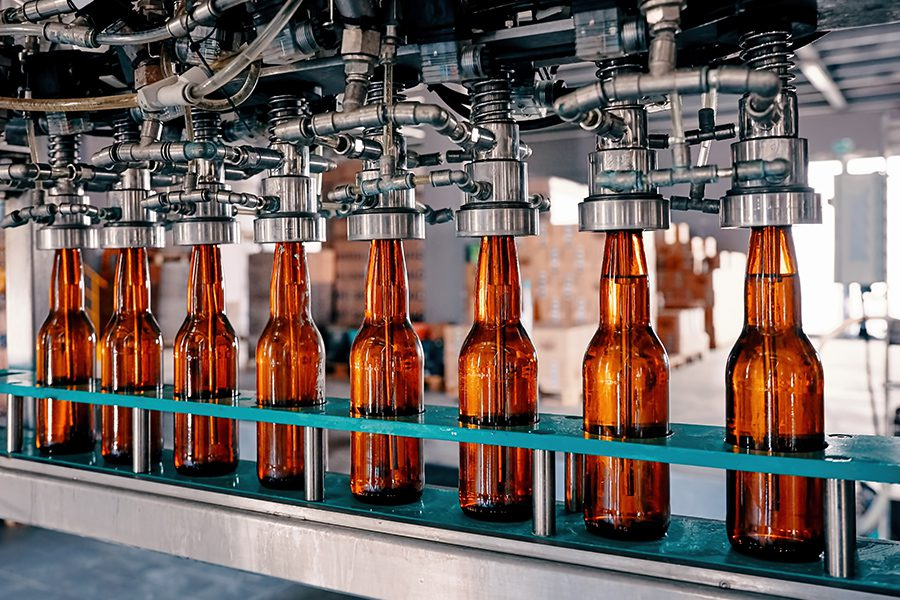 Specialized Business Insurance - Closeup View of Beer Bottles Being Filled on a Conveyor Belt in a Brewery