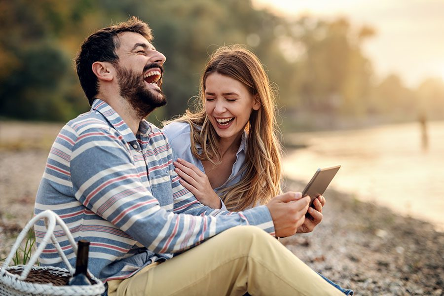 Blog - Young Couple Sitting By The Lake Holding A Tablet And Laughing