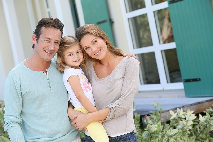 Personal Insurance - Smiling Young Family With Daughter Standing Outside Their Home